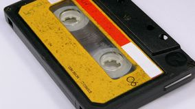 Audio Cassette Rotates on White Background. Vintage Yellow Retro tape cassette with a blank label. Old music. Close-up stock video footage
