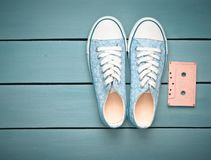 Audio cassette and sneakers shoes on a blue pastel background. Old-fashioned technologies. Top view. Flat lay.  royalty free stock photography