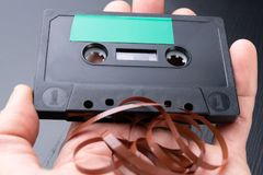 Audio cassette with space for text entry on the palm of your hand. Cassette without description. Dark background royalty free stock image