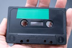 Audio cassette with space for text entry on the palm of your hand. Cassette without description. Dark background royalty free stock photos