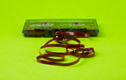 Audio cassette tape. Old  audio cassette with unwound tape on the paper Royalty Free Stock Photo