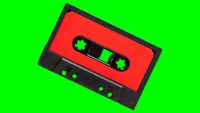 Audio cassette tape with blank red label pumping towards camera on greenscreen. Loopable royalty free illustration