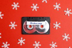 Audio cassette tape with decorative snowflakes on a red background. Music for Christmas mood. Nostalgia concept stock photography