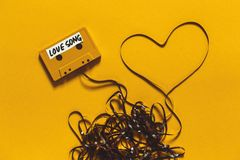 Audio Cassette Tape With The Inscription Love Song And Heart On A Yellow Background. Retro Technology Romance Concept