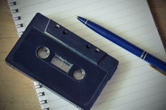 Audio cassette tape recorder and blue pen on book Royalty Free Stock Photo