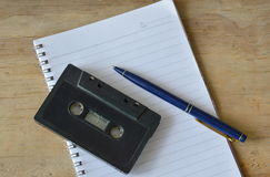Audio cassette tape recorder and blue pen on book Royalty Free Stock Image