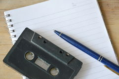 Audio cassette tape recorder and blue pen on book Stock Photos