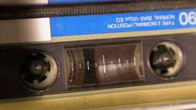 Audio Cassette in the Tape Recorder Playing and Rotates. Close-up. Vintage audio cassette tape with a blank label used for sound recording in a retro cassette stock video footage