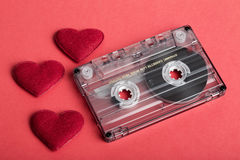 Audio cassette tape on red backgound with fabric heart Stock Photography