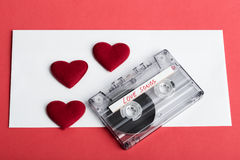 Audio cassette tape on red backgound with fabric heart Royalty Free Stock Photo