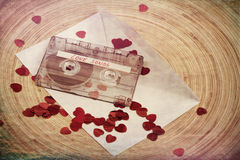 Audio cassette tape on red backgound with fabric heart Royalty Free Stock Photography