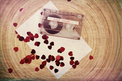 Audio cassette tape on red backgound with fabric heart Royalty Free Stock Images