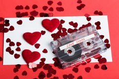 Audio cassette tape on red background with fabric heart Royalty Free Stock Image