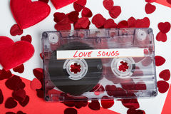 Audio cassette tape on red background with fabric heart Stock Image