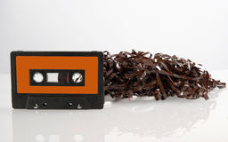 Audio cassette tape with reflection. Single black audio cassette and tangled tape  with its reflection  on white background. Included clipping path, so you can Stock Image