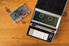 Audio cassette tape rolling in vintage player. On the desk, top view. Police interrogation sound recording retro technology concept for 1970s, 80s and 90s stock photo