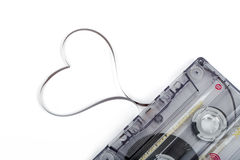 Audio cassette tape on white backgound. Film shaping heart Stock Photo