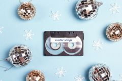 Audio cassette tape with winter holidays decorations on a blue background. Music for winter mood and party. Nostalgia concept royalty free stock photography