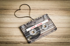 Audio cassette tape on wooden backgound. Film shaping heart Stock Image