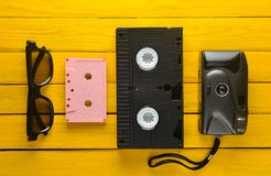 Audio cassette, vhs, 3d glasses, hipster film camera on a yellow wooden background. Retro devices from 80s. Top view.  Royalty Free Stock Images