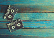 Audio cassettes and headphones on the blue wooden surface. Royalty Free Stock Photo