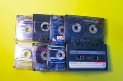 Audio cassettes are lined up on a yellow background.  royalty free stock photo