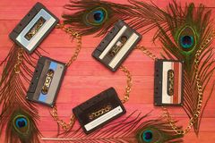 Audio cassettes tape clashing gold chain on pink wood. Composition stock images