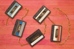 Audio cassettes tape clashing gold chain on pink wood. Composition royalty free stock photo