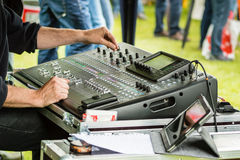 Audio control board. Hands using audio mixing board on outdoors concert stock photos