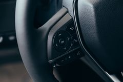 Audio control buttons on the steering wheel of a modern car. Close up Modern black steering wheel with multifunction buttons Integrated stereo controls pushes stock photos