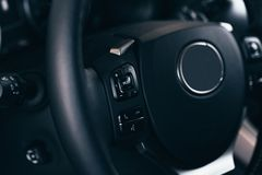 Audio control buttons on the steering wheel of a modern car. Close up Modern black steering wheel with multifunction buttons Integrated stereo controls pushes royalty free stock images