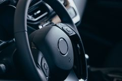 Audio control buttons on the steering wheel of a modern car. Close up Modern black steering wheel with multifunction buttons Integrated stereo controls pushes stock photo