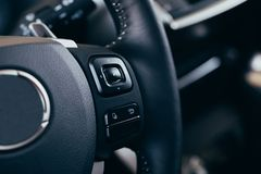 Audio control buttons on the steering wheel of a modern car. Close up Modern black steering wheel with multifunction buttons Integrated stereo controls pushes royalty free stock image