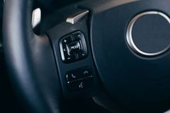Audio control buttons on the steering wheel of a modern car. Close up Modern black steering wheel with multifunction buttons Integrated stereo controls pushes royalty free stock photos