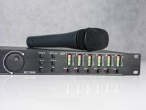 Audio DSP front panel with microphone. Audio DSP front panel turned on with all leds on. With natural reflection. Stage microphone unpluged on the top of DSP royalty free stock photo