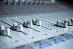Audio Engineer Mixing Board. Close up image of an audio mixing board with several channel volume sliders. Dials are also visible as blur in background royalty free stock photography