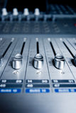 Audio Engineer Mixing Board. Close up image of an audio mixing board with several channel volume sliders. Dials are also visible as blur in background stock photo