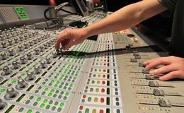 Audio engineer operating mixing console. With hands stock photography