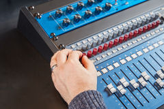 Audio engineer turning the knobs on the mixer Royalty Free Stock Photography