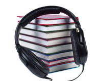 Audio headphones on a pile of books with color covers. Objects isolated white background stock photos