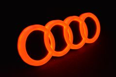 Audio inscription and Audi red auto logo - red color glowing. Very spectacular photo rings of Audi`s famous car in the world.100% original Audi car logo with Royalty Free Stock Photo