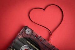 Audio kasety taśma na czerwonym backgound Ekranowy kształtujący serce Obrazy Royalty Free