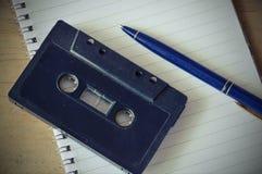 Audio kasety taśmy pisak i błękitny pióro na książce Zdjęcie Royalty Free