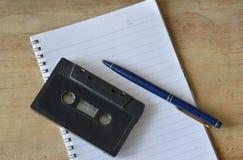 Audio kasety taśmy pisak i błękitny pióro na książce Obraz Royalty Free