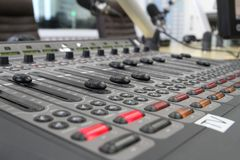 Audio mixer knobs during live TV telecast. Professional audio operator working on audio mixer knobs during live TV telecast stock photo