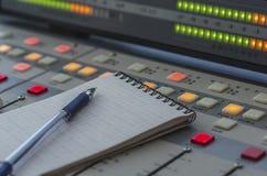 Audio mixer in radio studio. Audio mixer, notebook and pen in the radio studio Royalty Free Stock Photography
