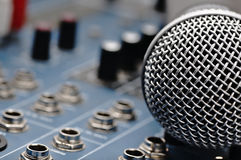 Audio mixer and a silver microphone. Sound console with buttons in the background and a dynamic microphone in the foreground stock photo