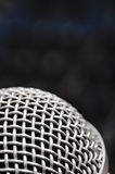 Audio mixer and a silver microphone. Sound console with buttons in the background and a dynamic microphone in the foreground royalty free stock photography