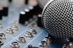 Audio mixer and a silver microphone. Sound console with buttons in the background and a dynamic microphone in the foreground royalty free stock images