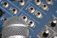 Audio mixer and a silver microphone. Sound console with buttons in the background and a dynamic microphone in the foreground stock photos